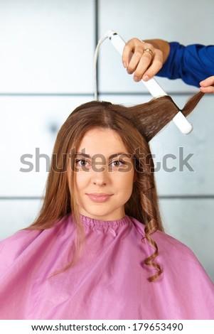 Hair salon. Woman haircut. Use of straightener. - stock photo