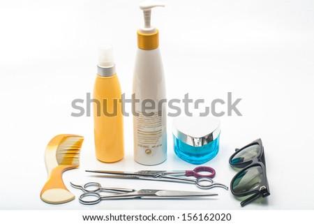 Hair scissors whith beauty cream bottle comb and eyeglasses on white, barber - stock photo