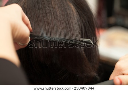 Hair straightening by a hairdresser in a professional salon, closeup shot. - stock photo