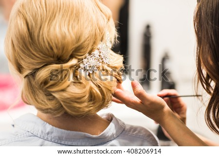 Hair stylist makes the bride before a wedding - stock photo