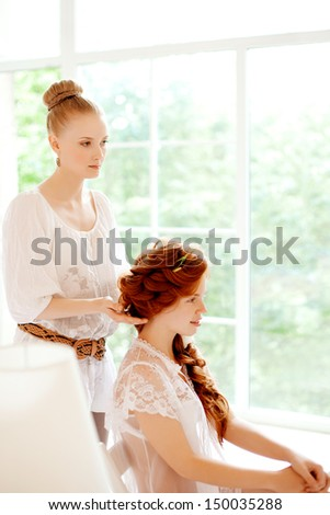 Hair stylist makes the bride before the wedding - stock photo