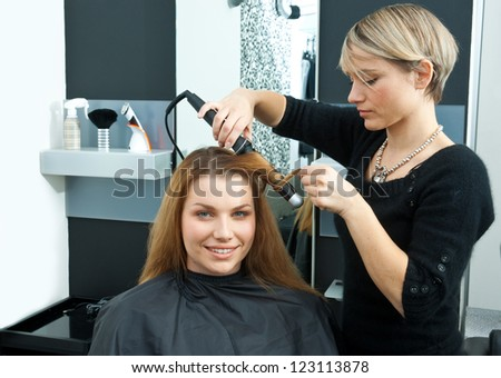 hair stylist making new haircut to brunette woman in salon - stock photo
