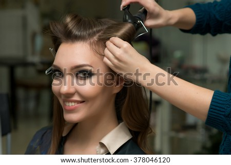 Hair stylist making ringlets to brunette woman. Hairdresser working with beautiful woman hair in hairdressing salon.  - stock photo