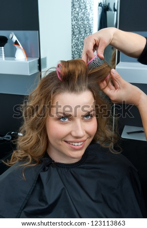 hair stylist putting rollers in woman hair
