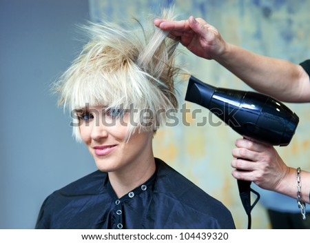 hair stylist using dryer on woman wet hair in salon - stock photo