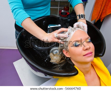 hair stylist washing woman hair in salon pool