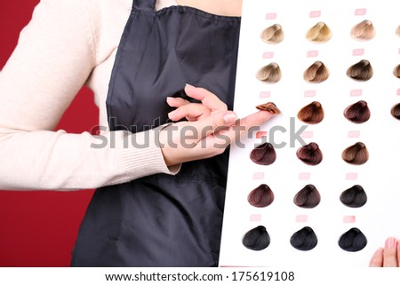 Hair stylist with hair samples of different colors, close-up - stock photo