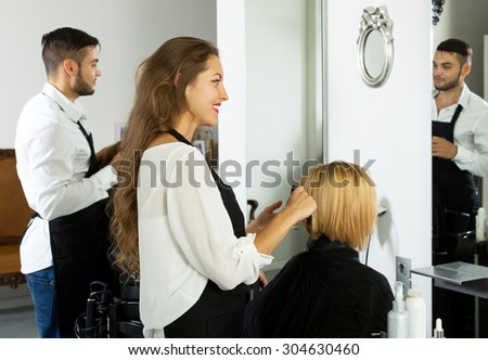 Hair stylist working on haircut for female client
