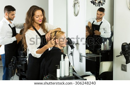 Hair stylist working on haircut for happy client - stock photo