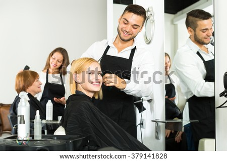 Hair stylist working on haircut for young beautiful woman. Focus on the woman - stock photo