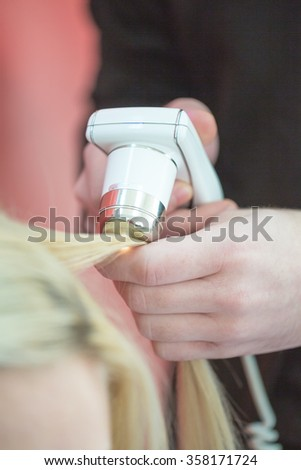 hair treatment. hair testing. man's hand with the device for testing fiber optic links