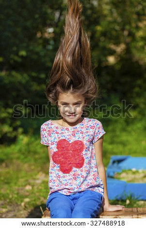 Hair Up. Close up portrait of a beautiful nine year old little girl in autumn park - stock photo