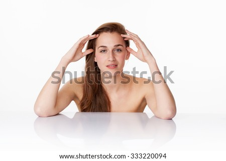 haircare and skincare concept - beautiful 20s woman with long brown hair touching her face on clear white glass at beauty spa,studio shot - stock photo