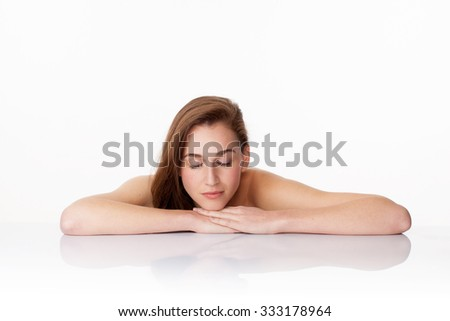 haircare and skincare concept - relaxing 20s woman with long brown hair closing her eyes on clear white glass for relaxation and meditation,studio shot - stock photo
