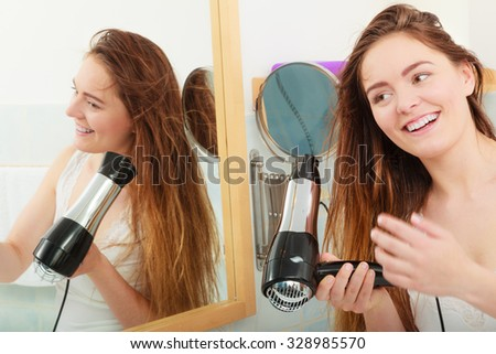 Haircare. Beautiful long haired woman drying hair in bathroom