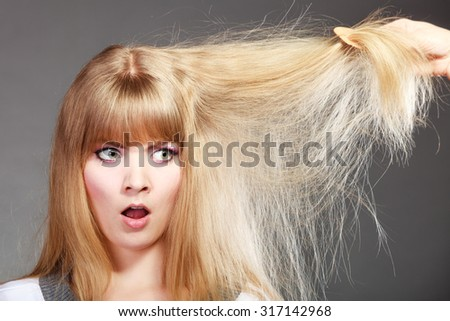 Haircare. Blonde woman with her damaged dry hair angry face expression gray background - stock photo