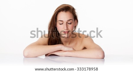 haircare concept - elegant 20s woman with long brown hair closing her eyes in leaning on clear white glass for relaxation and imagination,studio shot - stock photo
