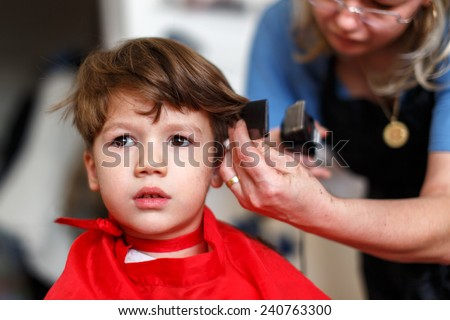 Haircut for little boy, mother cut hair for son at home - stock photo