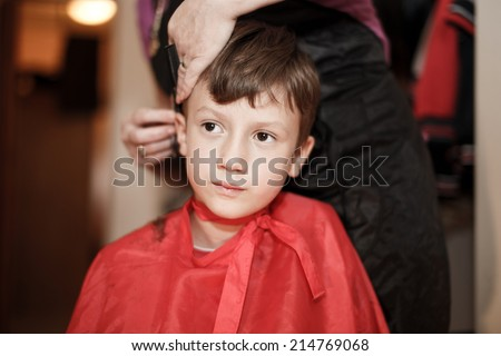 Haircut for little caucasian boy at professional barber - stock photo