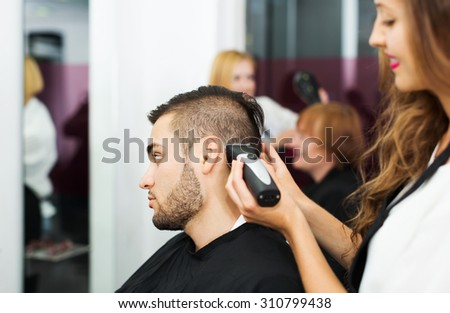 Haircutter makes the haircut for man in the hairdressing salon - stock photo