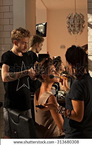Hairdresser and make-up artist works in a beauty salon with a beautiful young asian woman a client. Preparing the model around mirror- to do hair and makeup at the same time backstage- stock photo. - stock photo