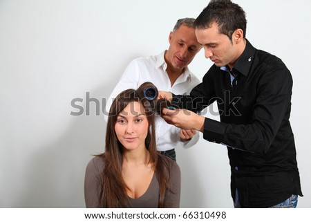 Hairdresser and trainee putting hair-curlers - stock photo