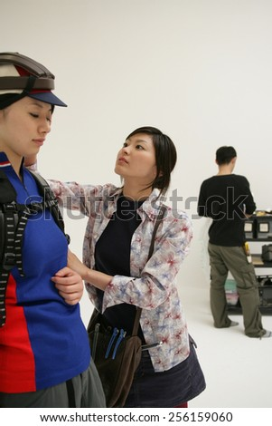 Hairdresser assisting a female fashion model at a photo shoot