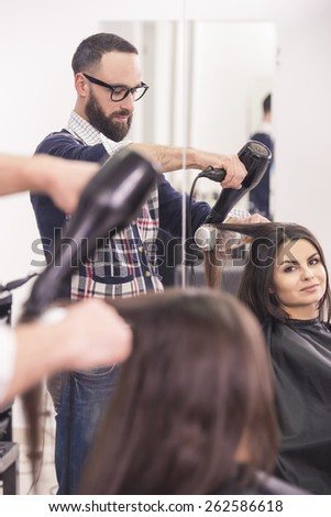 Hairdresser blow dry beautiful  woman hair in hairdressing salon. - stock photo