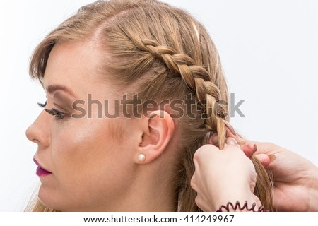 Hairdresser braids long straight hair isolated on white background.