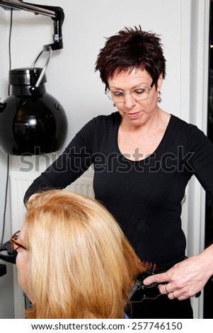 hairdresser brings the hair in model with a brush  - stock photo