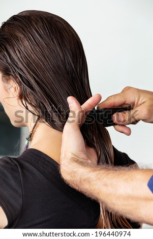 Hairdresser combing client's wet hair in salon