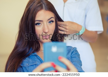 Hairdresser combing hair woman with mobile phone in hairdressing salon. Concept of fashion and beauty. Positive emotion - stock photo