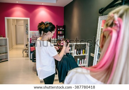 Hairdresser curling woman hair with curlers in a hair and beauty salon - stock photo