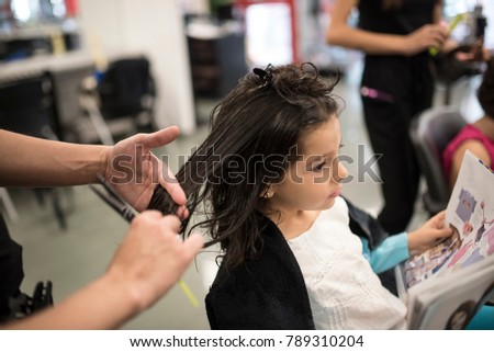 Hairdresser cuts and combing little girls hair
