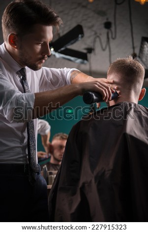 hairdresser  cuts    hair  with hair clipper on back of the head of handsome satisfied  client in  professional  hairdressing salon low angle