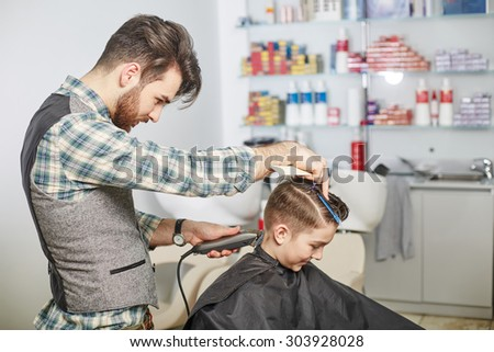 hairdresser cuts hair with scissors on crown of handsome satisfied client in professional hairdressing salon  - stock photo