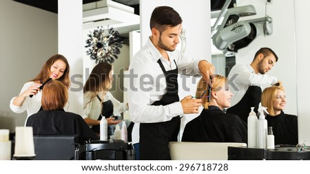 Hairdresser cuts young girl's hair in the beauty salon - stock photo