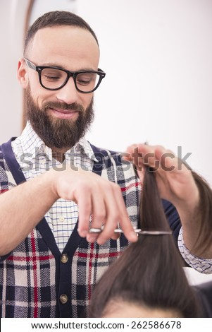 Hairdresser cutting brunette hair with scissors in hairdressing salon. - stock photo