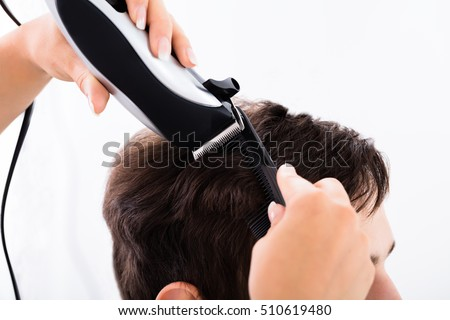 Hairdresser Cutting Person's Hair With Electric Trimmer