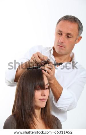 Hairdresser cutting woman's hair - stock photo