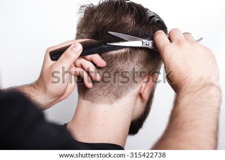 Hairdresser does new haircut, with black comb and scissors, for bearded man, on white background in studio, close up - stock photo