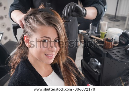 hairdresser doing haircut for woman in hairdressing salon. Concept of fashion and beauty - stock photo