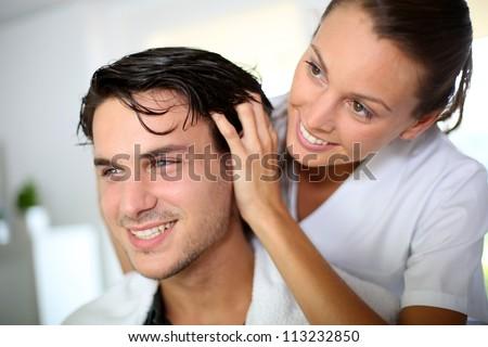 Hairdresser doing head massage to customer - stock photo