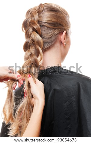 hairdresser doing up one's hair in a plait. isolated on white background