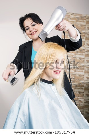 Hairdresser dries the hair dryer blond long hair - stock photo