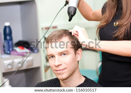 hairdresser dries the hair guy in a beauty salon
