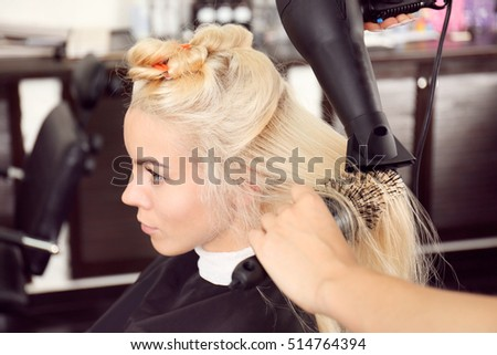Hairdresser drying blonde's hair at salon