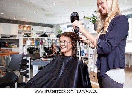 Hairdresser drying female customer's hair in beauty salon - stock photo