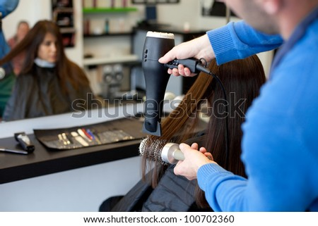 Hairdresser drying woman's hair using hair dryer and round brush. Selective focus. - stock photo