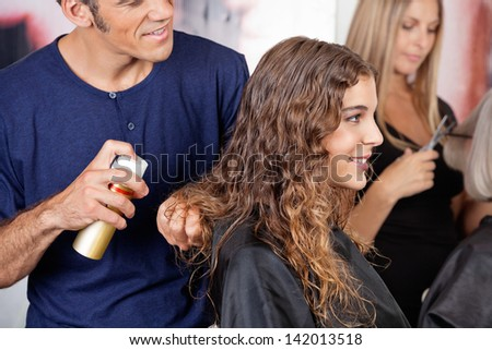 Hairdresser fixing woman's hair with hairspray in salon
